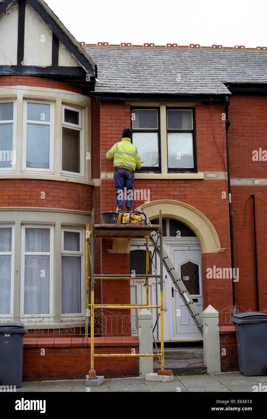 Man on scaffold tower repointing the brickwork on the front of a terraced house - Stock Image