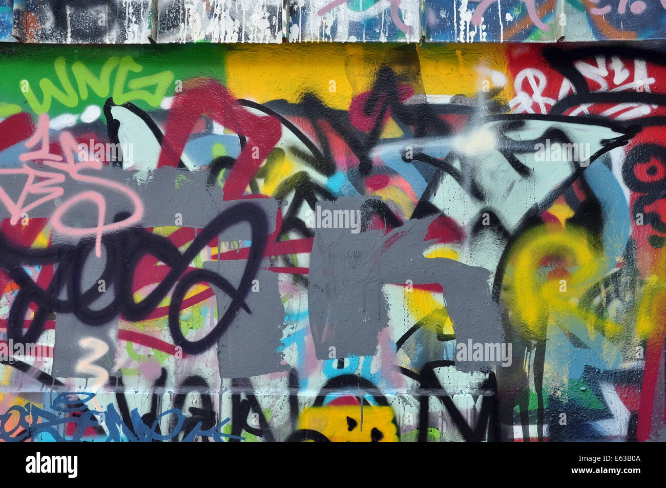 Textured wall covered with messy graffiti and tags abstract urban art background stock