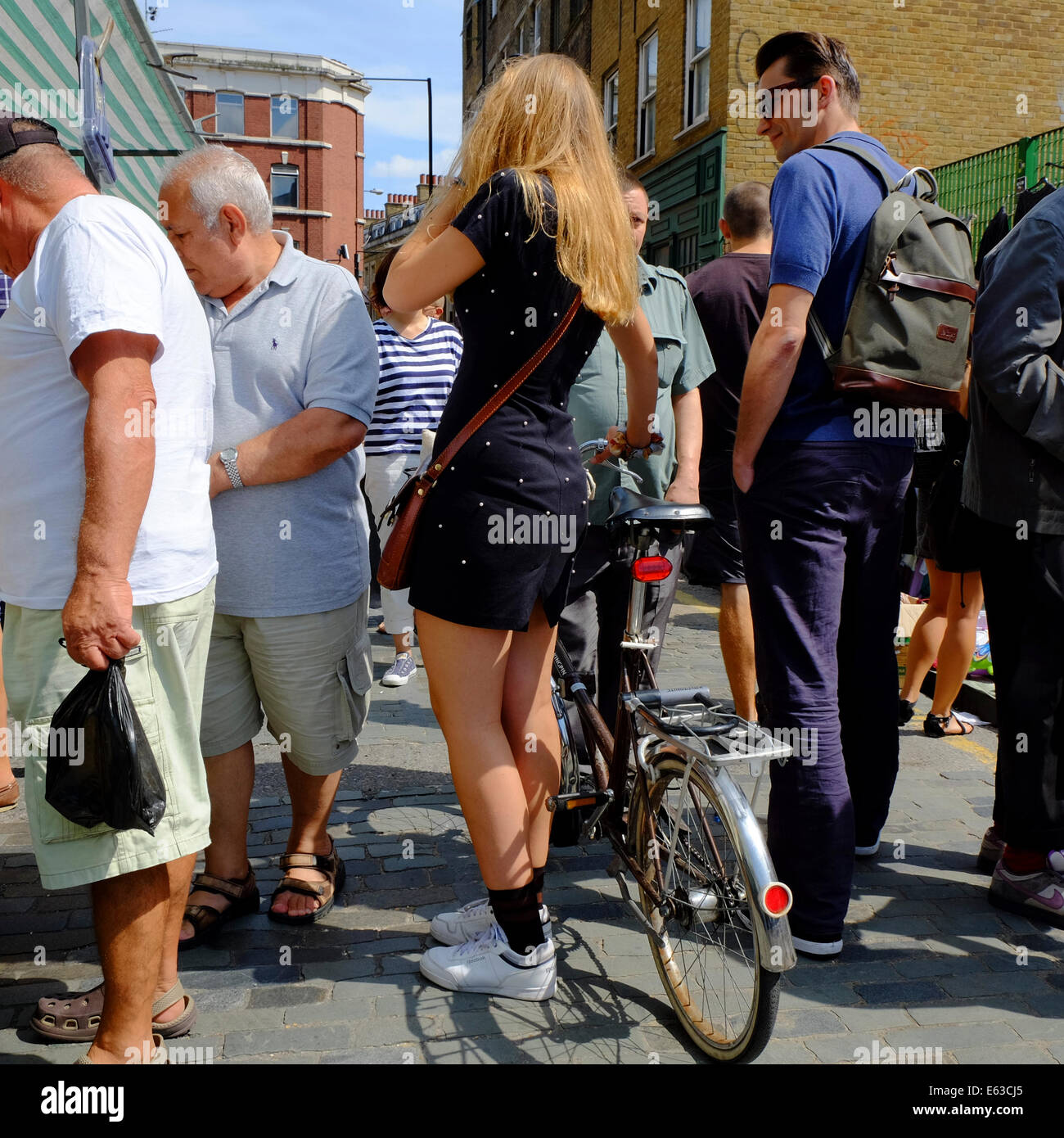 Attractive young woman in mini dress with bicycle taking on her phone in a crowded market in Shoreditch, London, - Stock Image