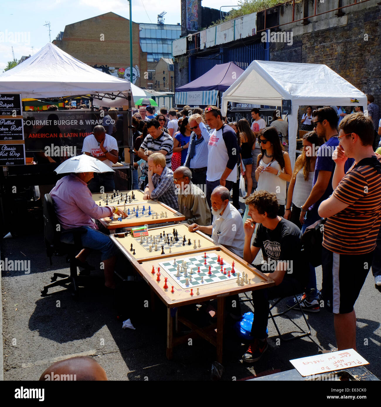 man playing chess against 4 others, all at the same time in Brick lane, Shoreditch, London, England - Stock Image