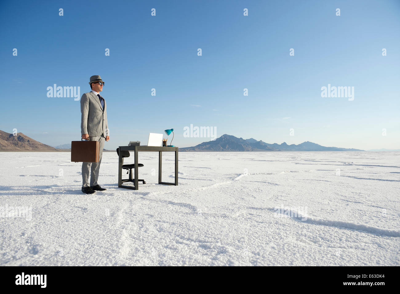 Businessman standing next to mobile office desk outdoors on dramatic white desert landscape - Stock Image