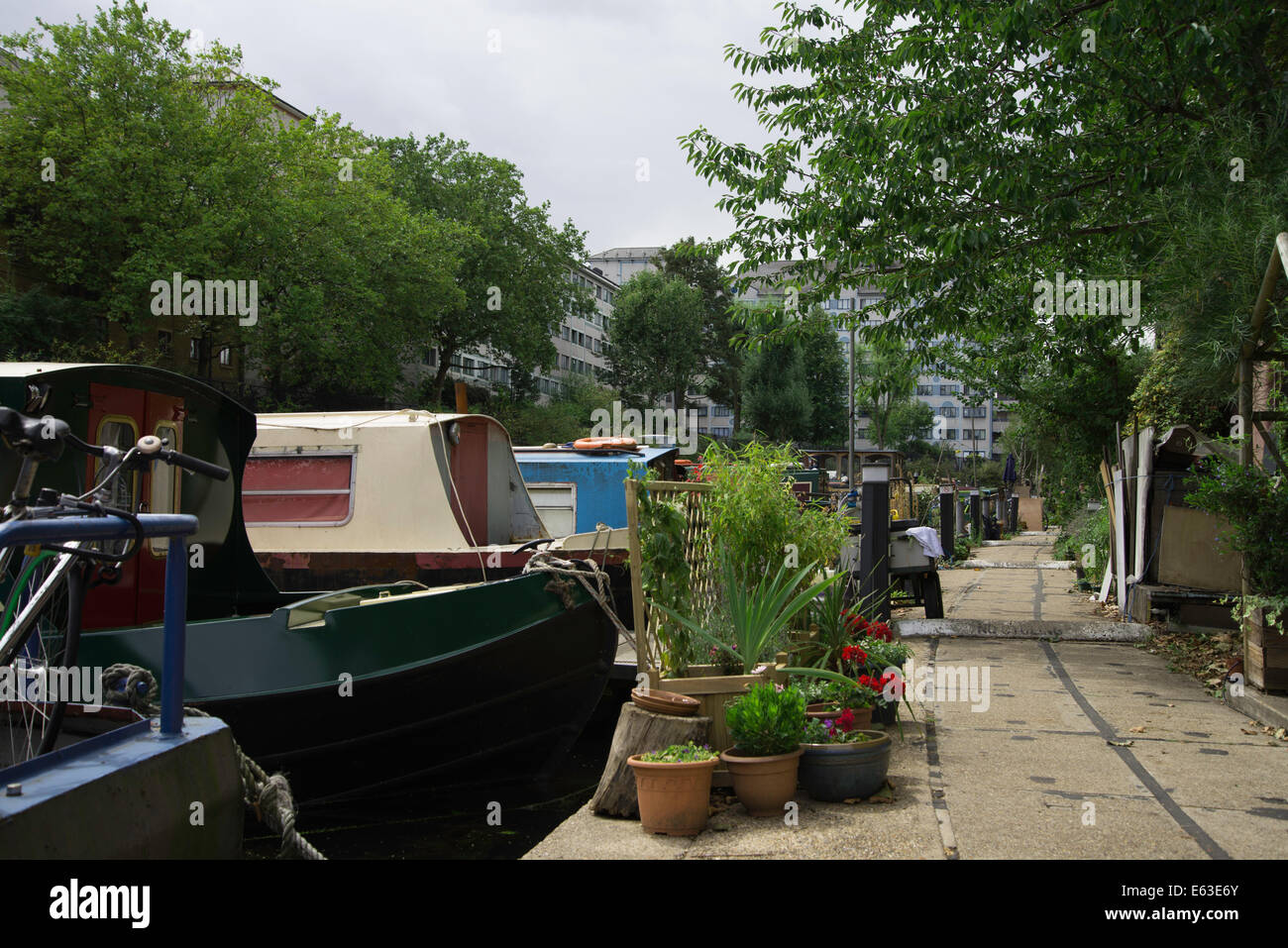 Regents Canal towpath with houseboats plants and overhanging trees - Stock Image