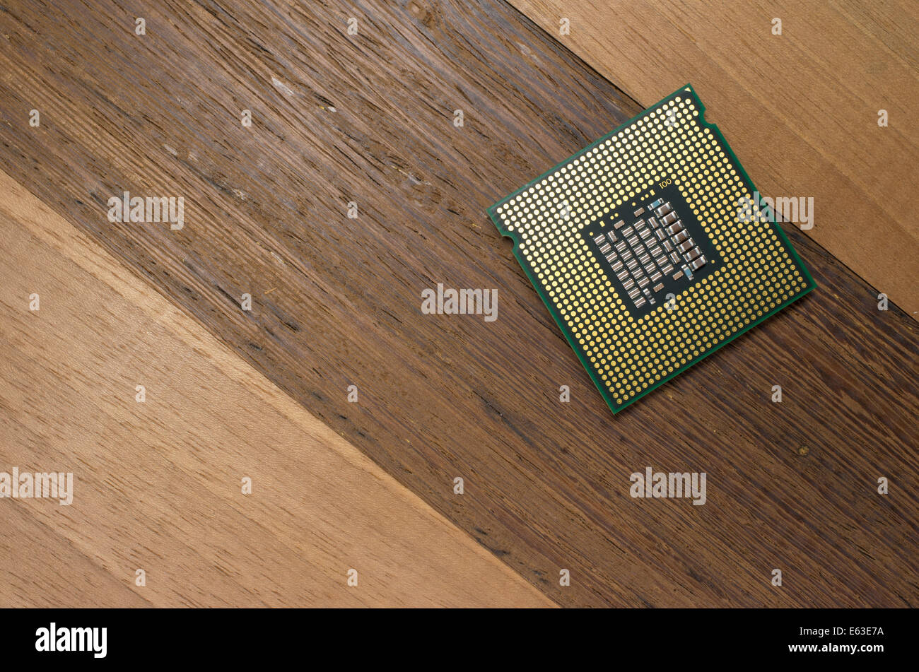 Intel Core 2 Quad cpu back, close up on a wood background - Stock Image