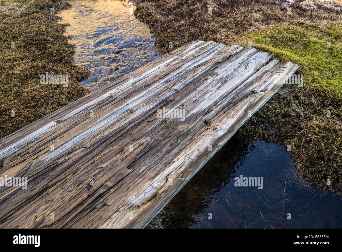 Wooden plank used as a bridge to cross over a creek, Stokksnes, Eastern Iceland - Stock Image