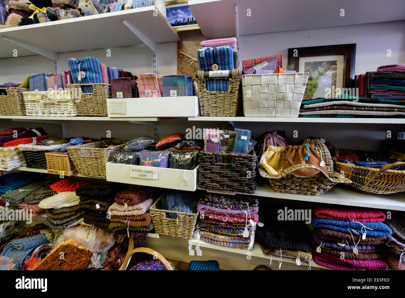 Hebridean tweed goods and souvenirs for sale on shelves in a gift shop selling local woolen crafts. Isle of Lewis - Stock Image