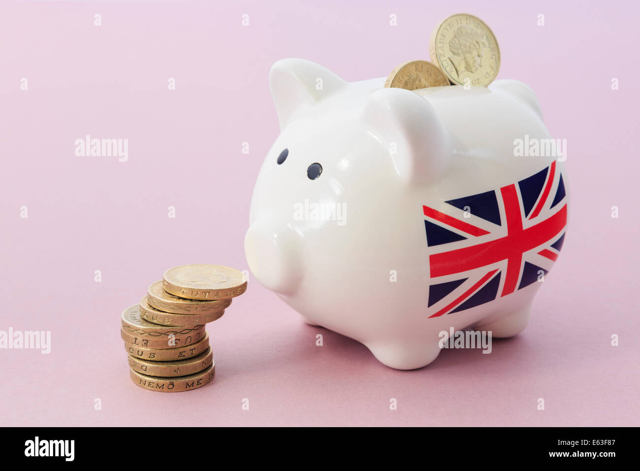 British Union Jack on Piggy bank looking at a pile of sterling pounds  pound coins illustrating savings and financial - Stock Image