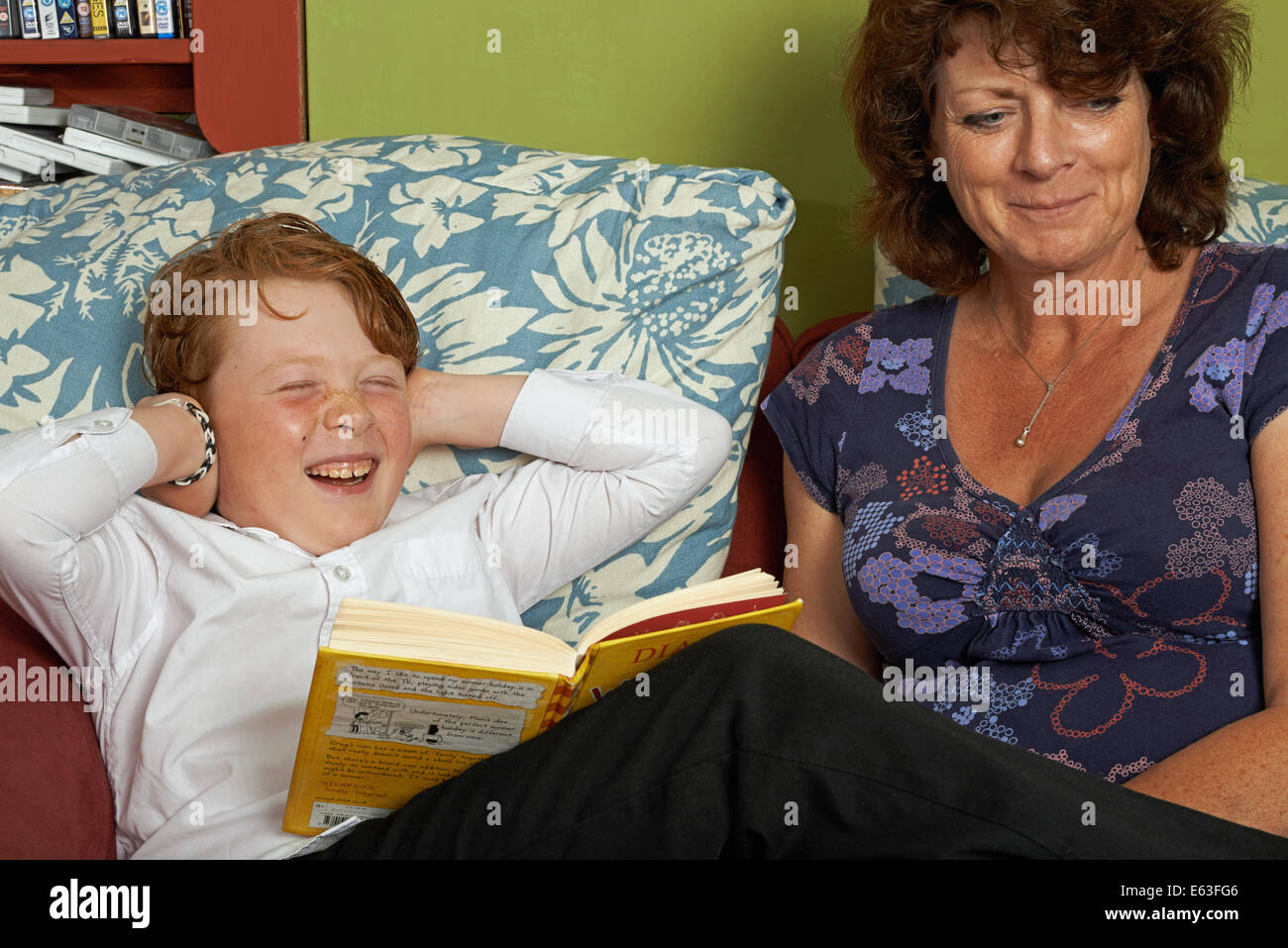 Single mother has just told her son that he can not go outside to play until he finishes his school homework - Stock Image