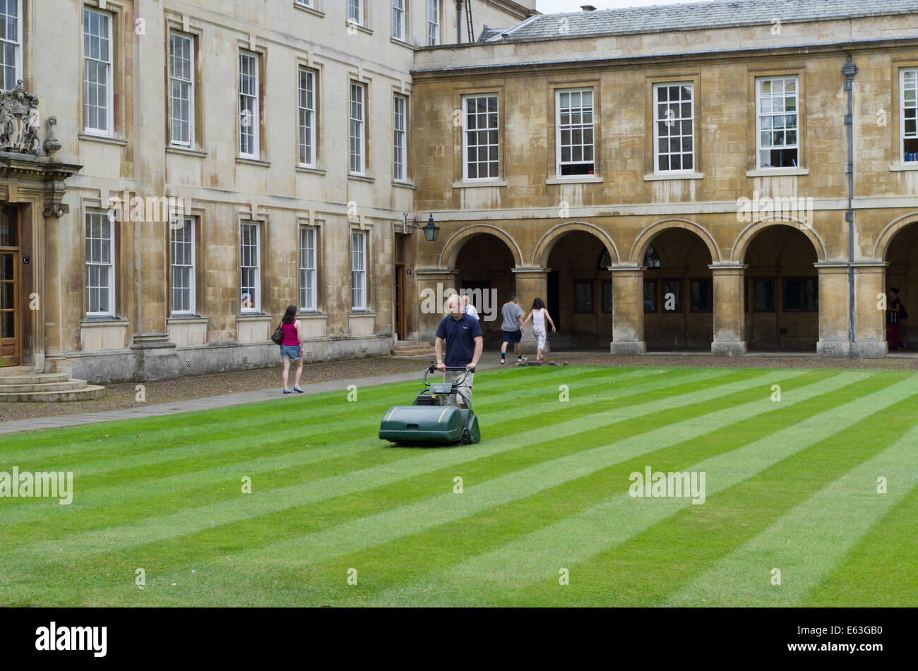 Gardener mowing the lawn within Emmanuel College, Cambridge, UK - Stock Image