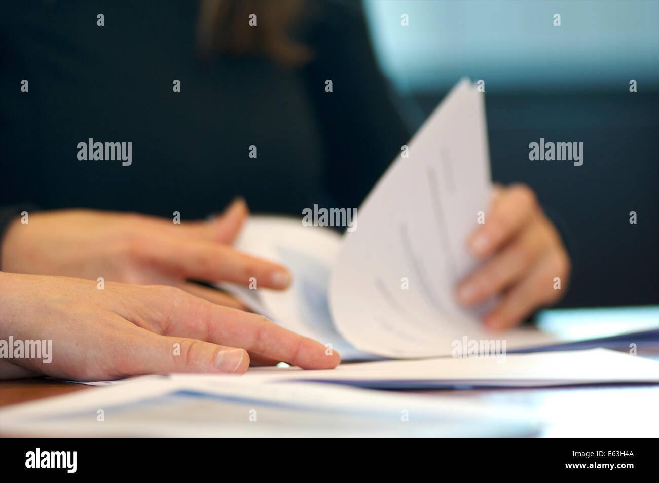 Hands and documents on the table in an office during a meeting - Stock Image