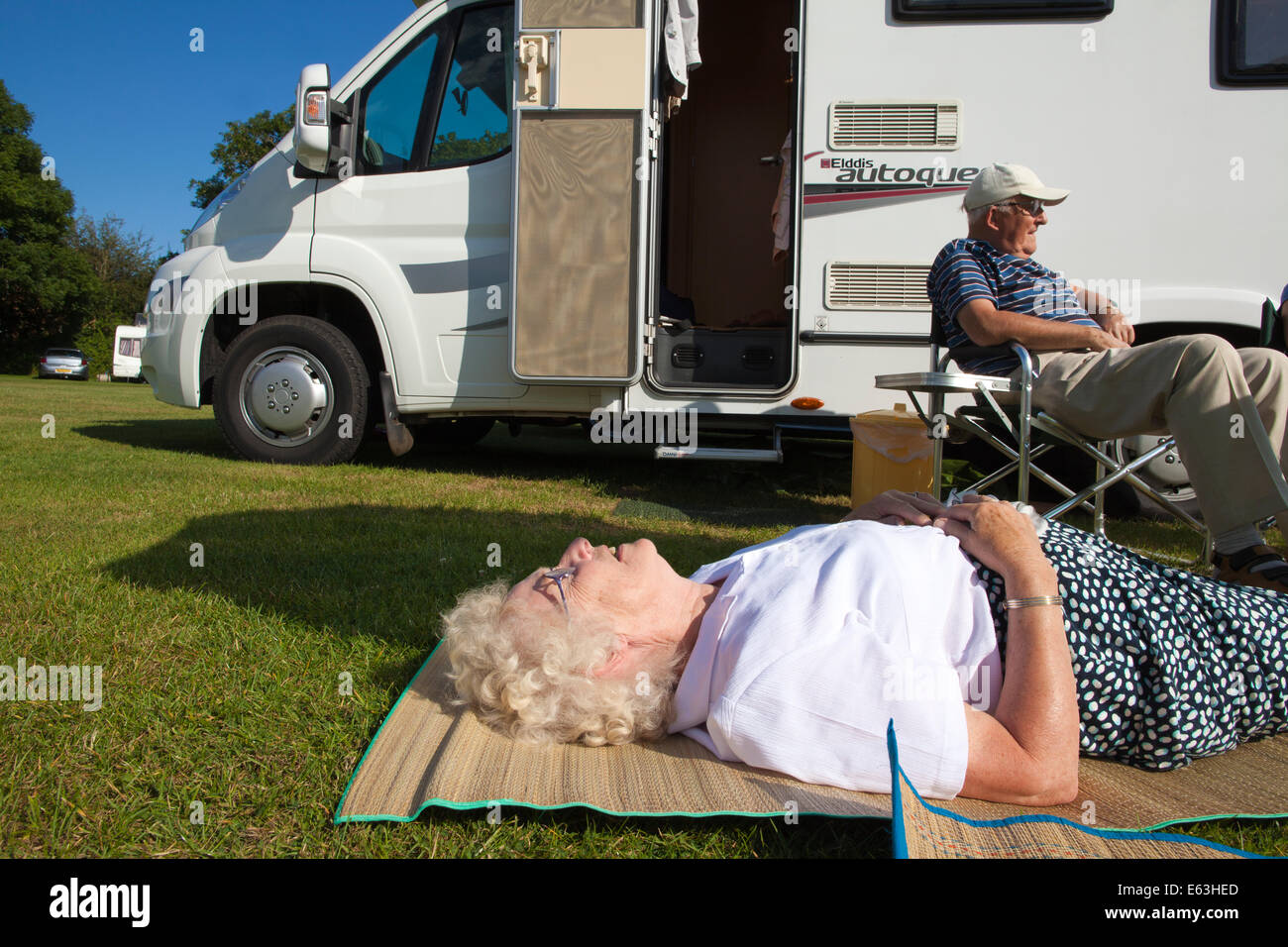Elderly woman and man relaxing in the sunshine outside their caravan whilst enjoying retirement in Devon, England, - Stock Image