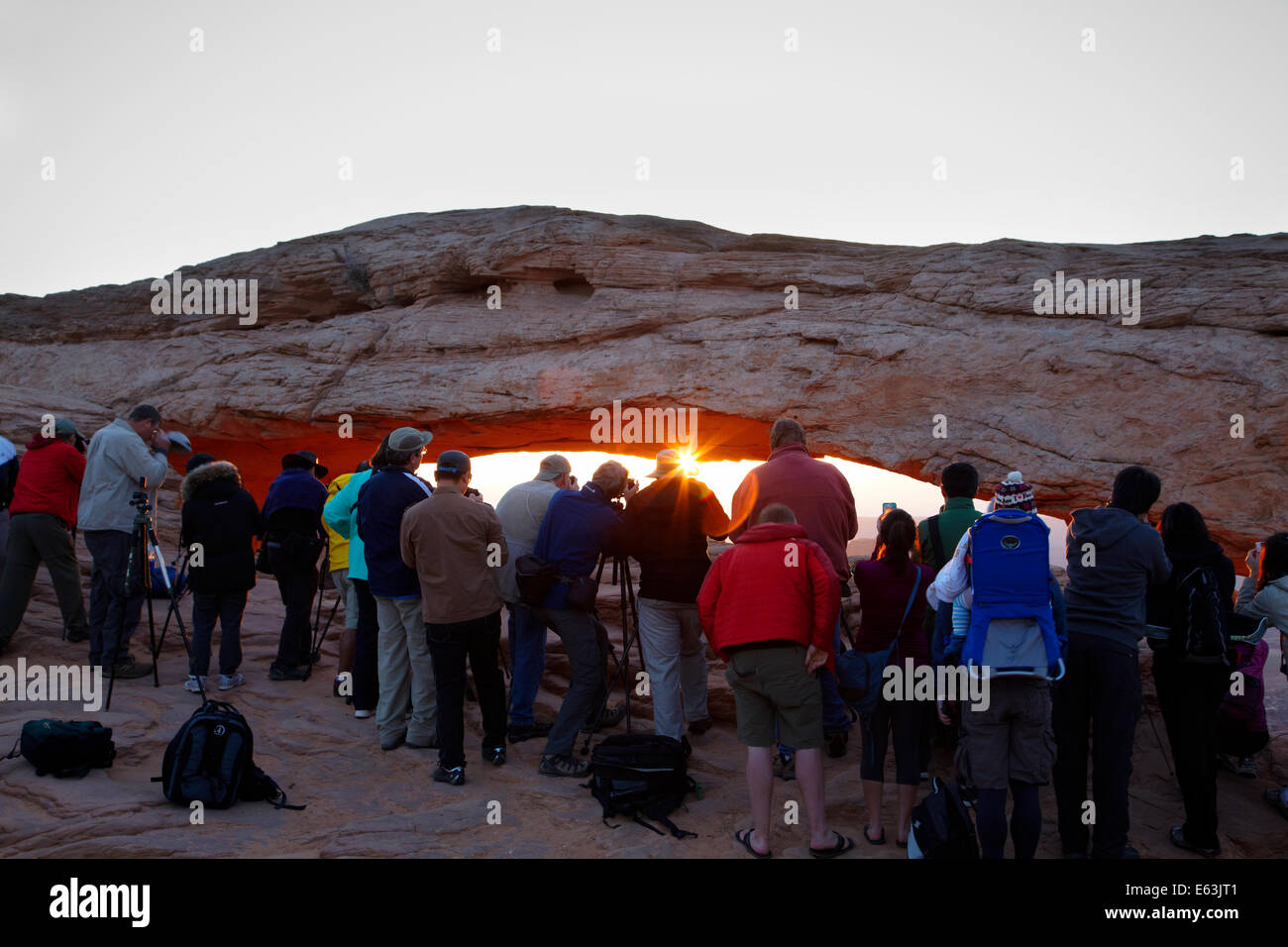 Crowd of photographers shooting sunrise under Mesa Arch, Canyonlands National Park, Utah, USA - Stock Image