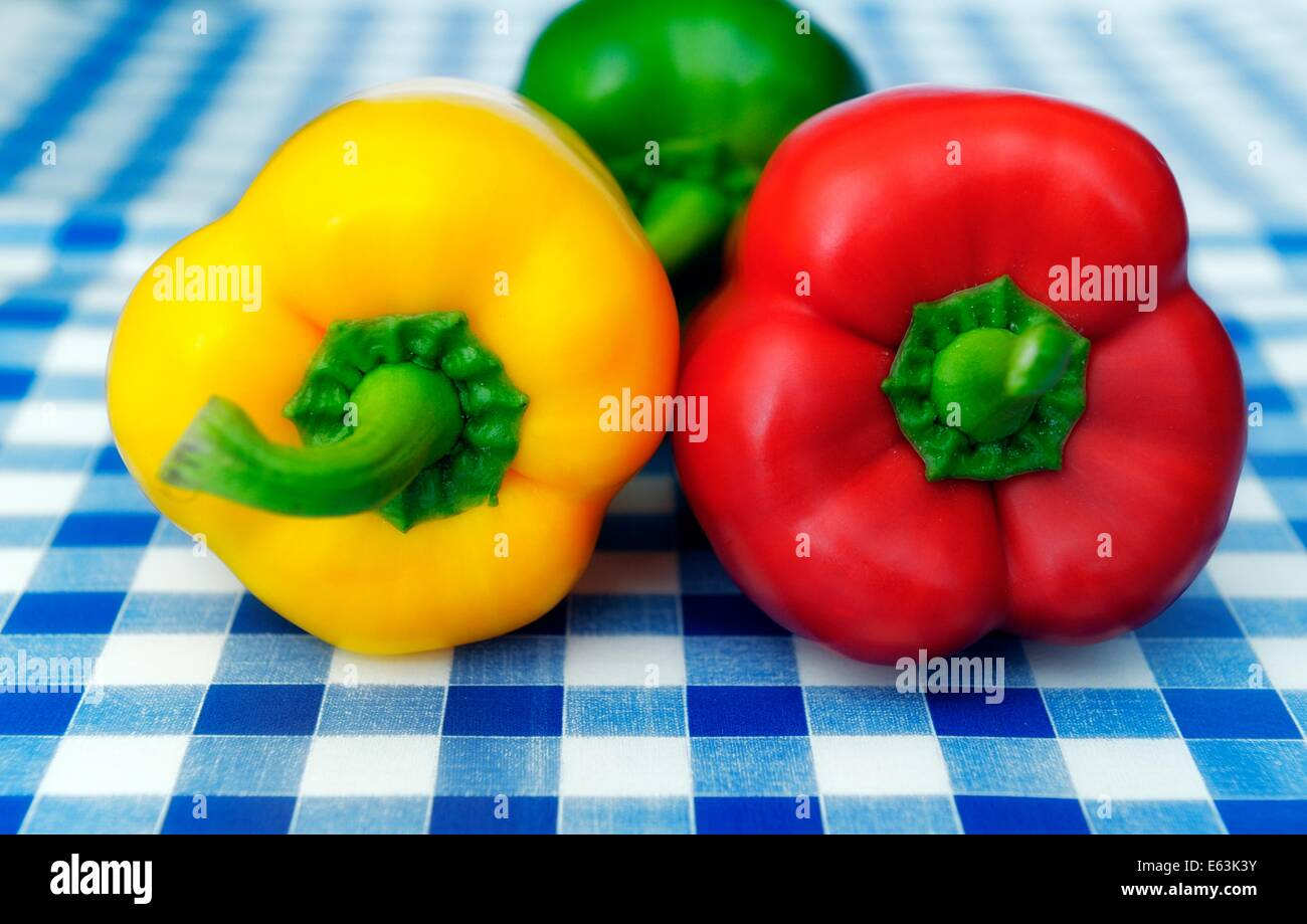 A Red Yellow And Green Bell Peppers On A Blue Gingham Tablecloth Background    Stock Image