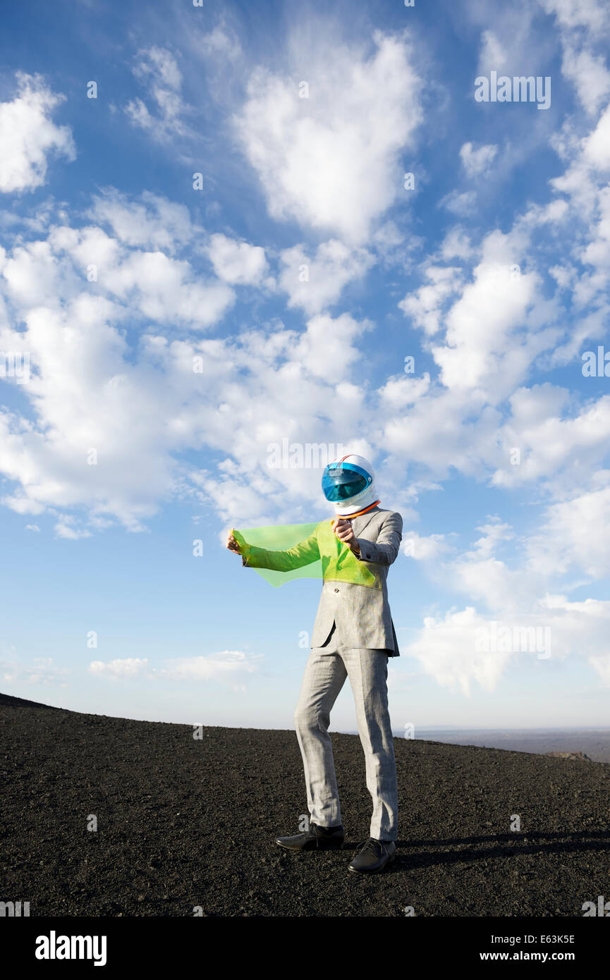 Explorer businessman in lunar landscape reads electronic map on future technology flexible display tablet - Stock Image
