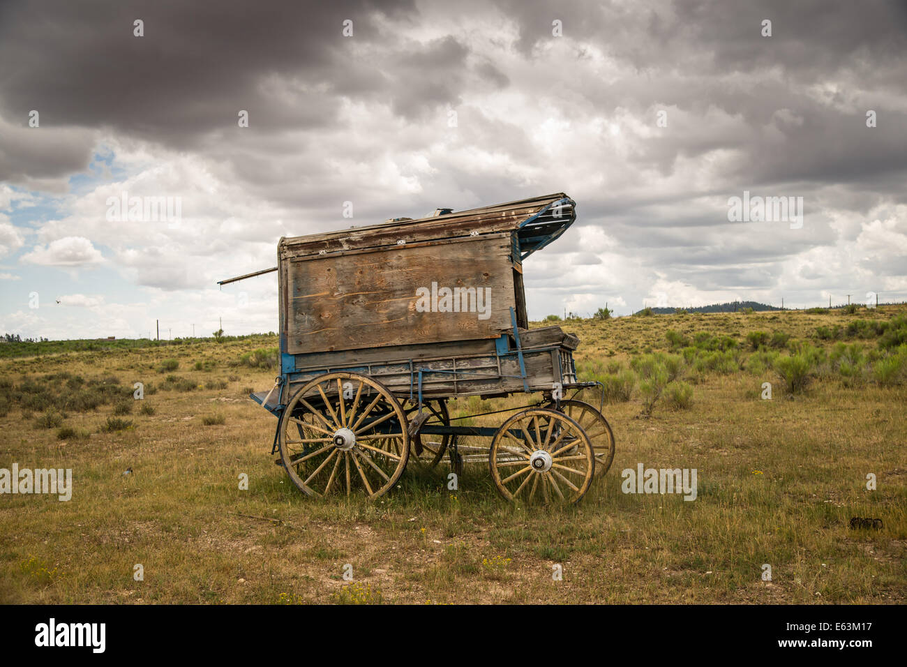 An old west sheriff's wagon sits on the lonesome frontier prairie as storm clouds gather in the distance. Stock Photo