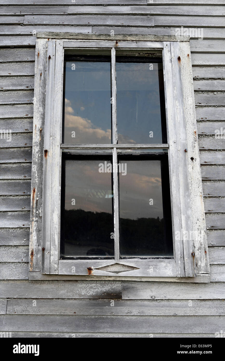 Weather worn window casing on old building in Machais, Maine. - Stock Image