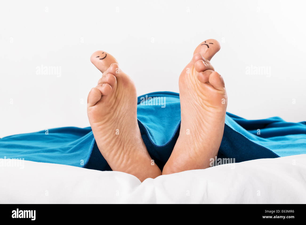 Human feet with smiley and grumpy drawn on them - Stock Image