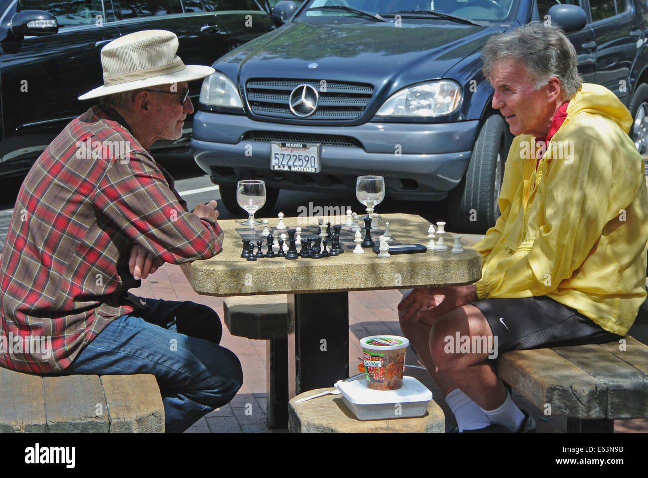 two adult males playing chess on table in downtown Mill Valley Park - Stock Image