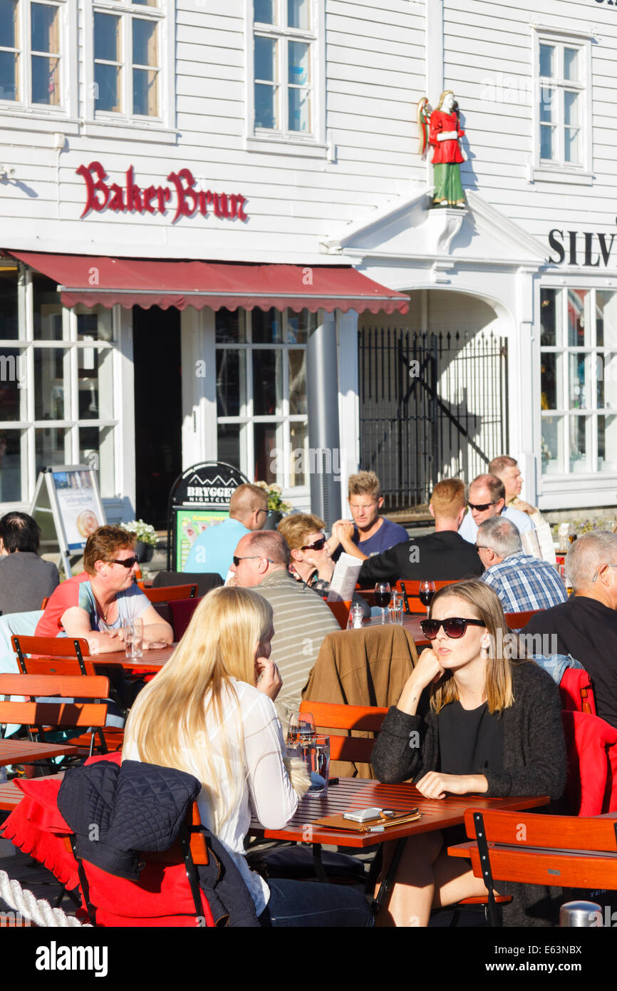 People sitting at outdoor terraces of the pubs at Bryggen wharf, Bergen, Norway - Stock Image