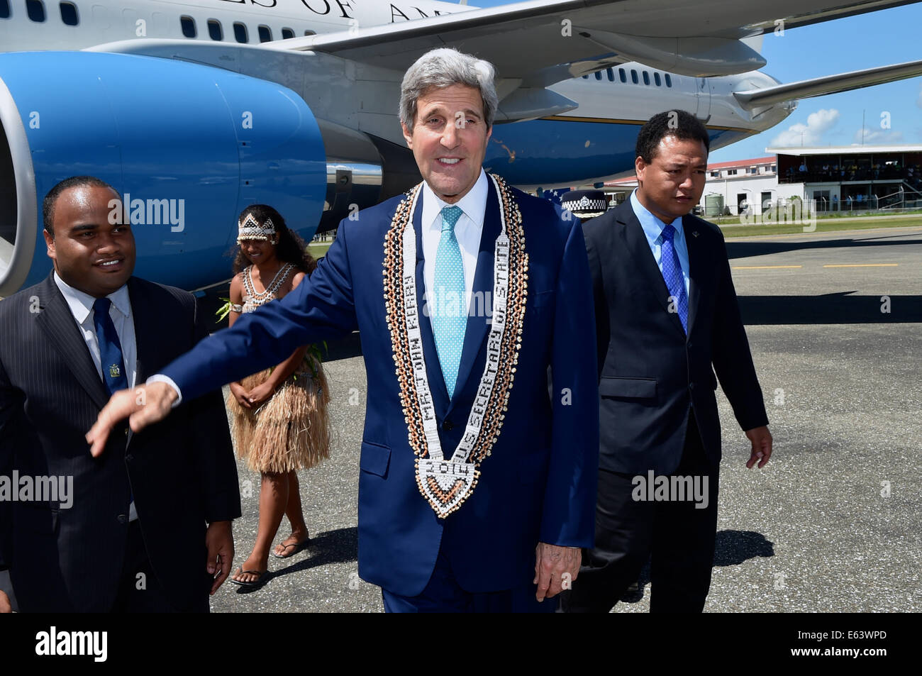 US Secretary of State John Kerry receives a traditional necklace as he arrives at Henderson International Airport - Stock Image