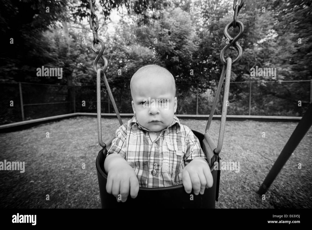 a male toddler sits in a swing at a park in the summer with a serious look on his face Stock Photo