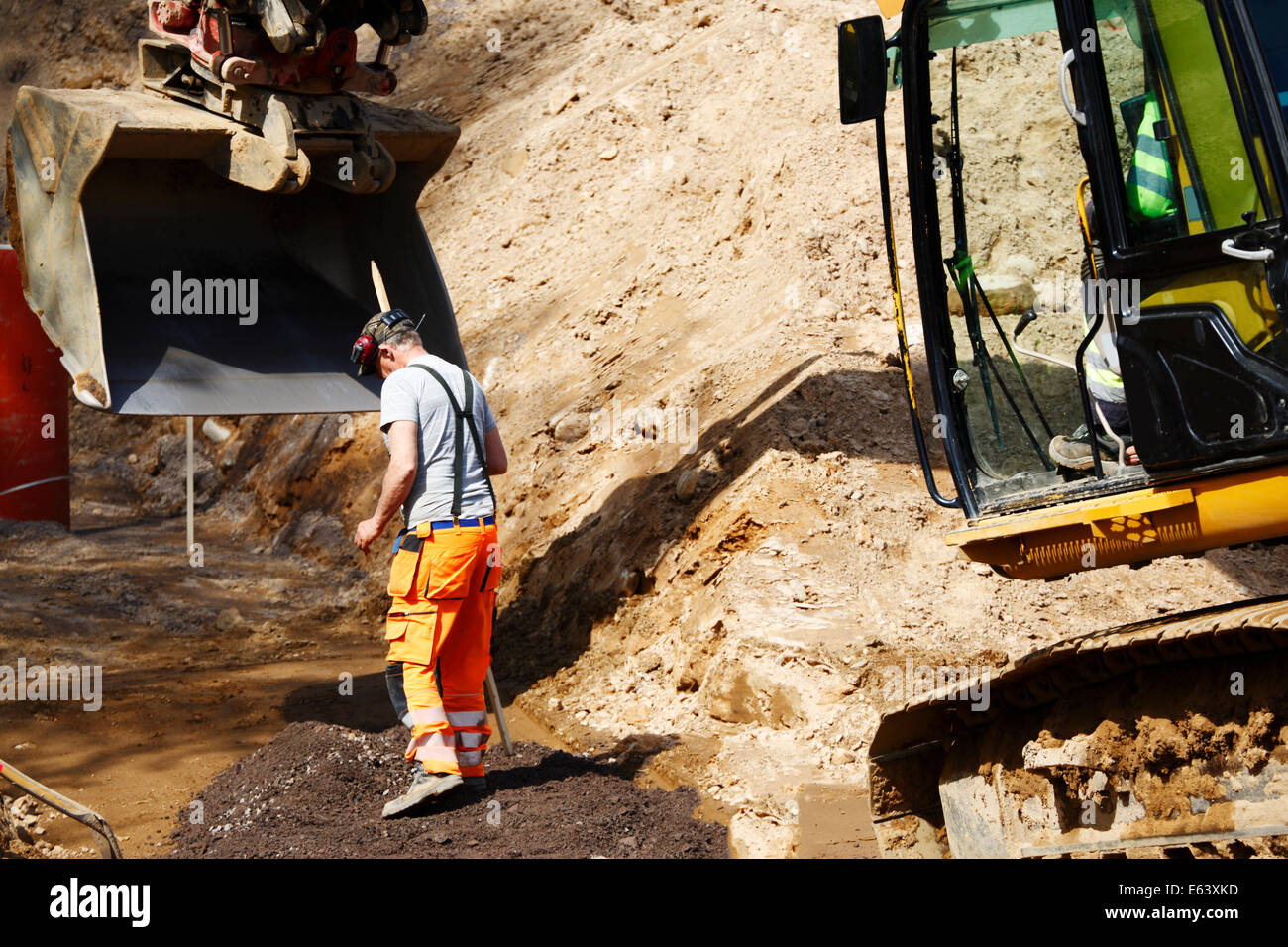 building-worker and bulldozer in excavating works, close-ups - Stock Image