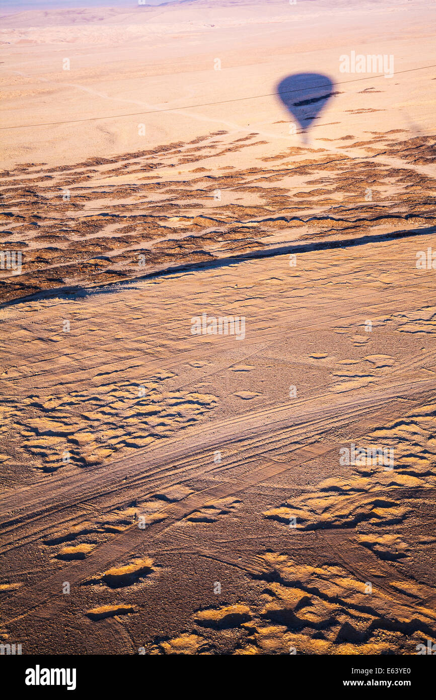 The shadow of a hot air balloon flying over the desert of the West Bank of the Nile in Egypt at sunrise. - Stock Image