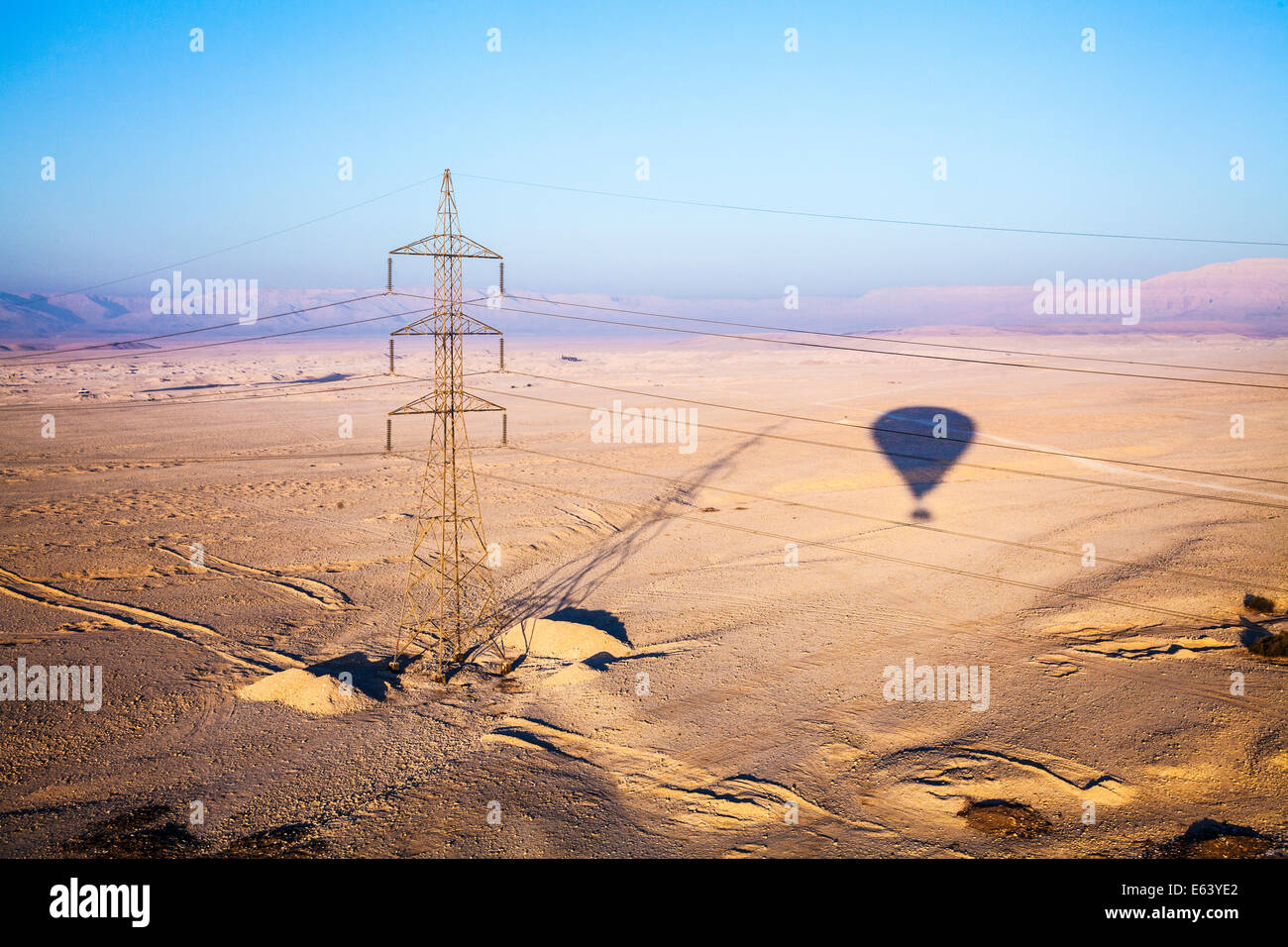 The shadow of a hot air balloon and an electricity pylon over the desert of the West Bank of the Nile in Egypt at - Stock Image