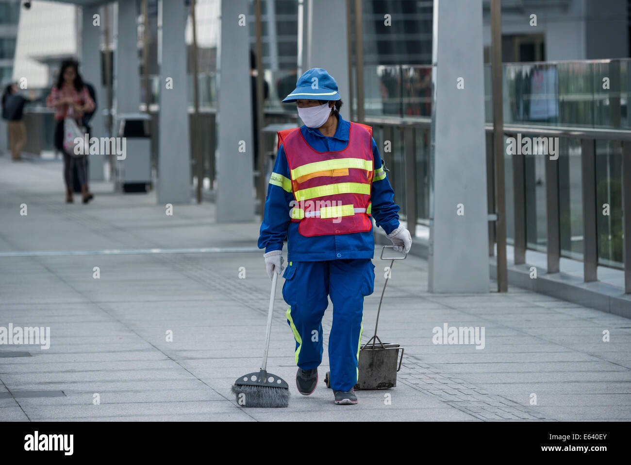 Female street cleaner wearing a safety vest, mask and holding a sweeping tool, Shanghai, China - Stock Image