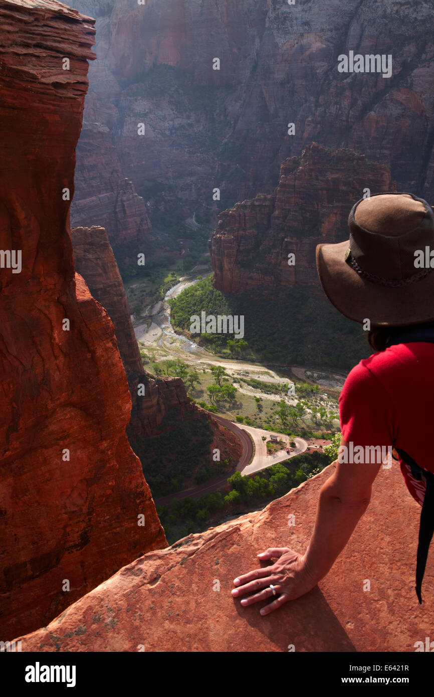 Hiker looking off sheer cliff into Zion Canyon from Scout Lookout, Angels Landing track, Zion National Park, Utah, - Stock Image
