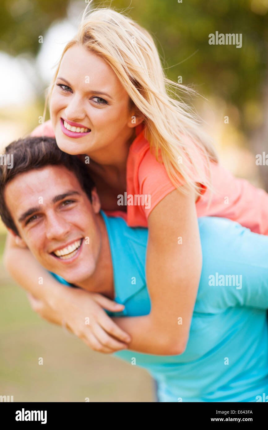 cheerful young woman enjoying piggyback ride on boyfriends back outdoors - Stock Image