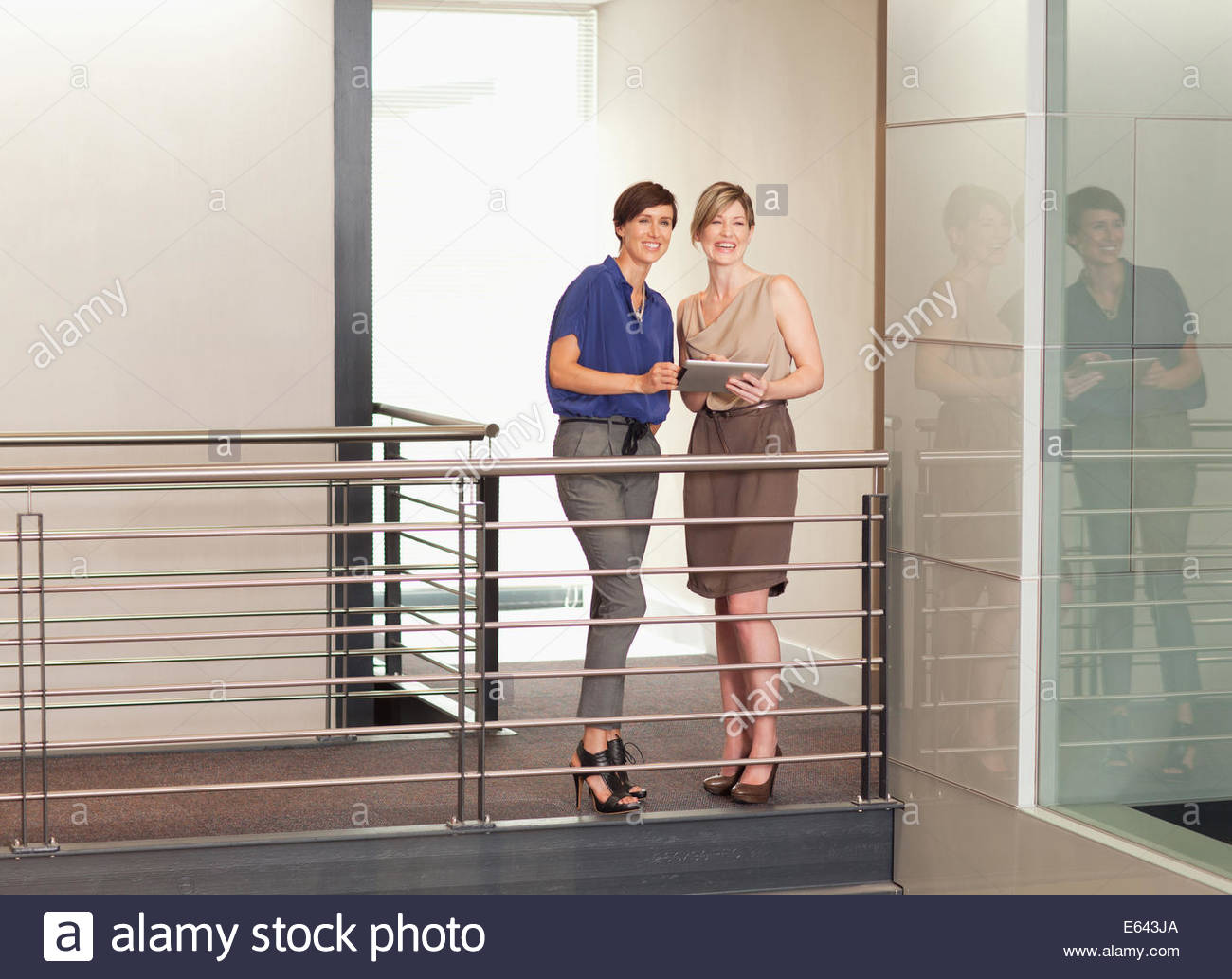 Businesswomen with digital tablet on elevated walkway in office - Stock Image