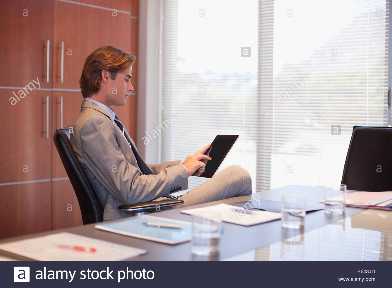 Businessman using digital tablet in office - Stock Image