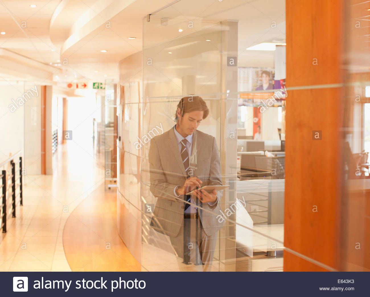 Businessman with digital tablet in office window - Stock Image