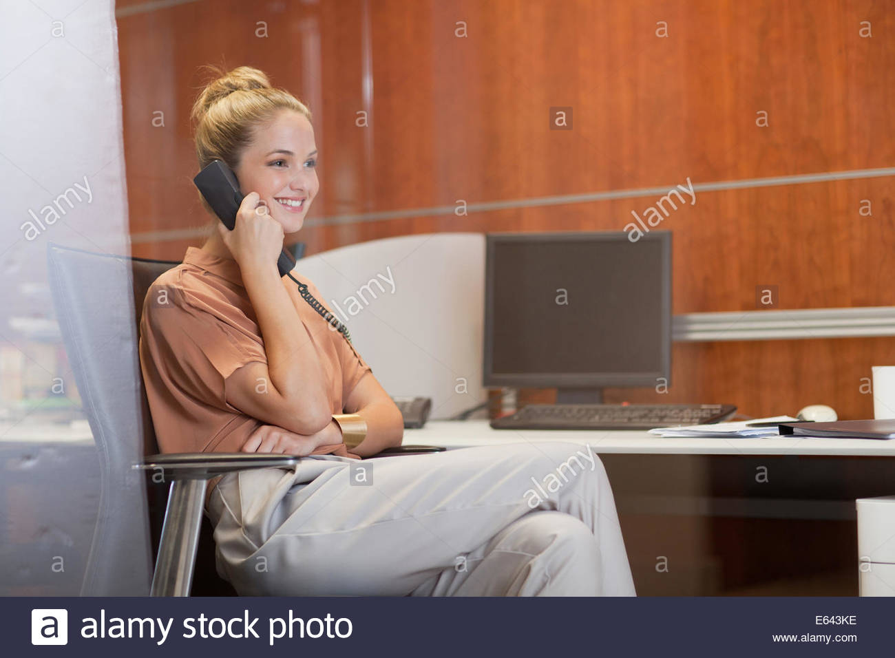 Smiling businesswoman talking on telephone in office - Stock Image