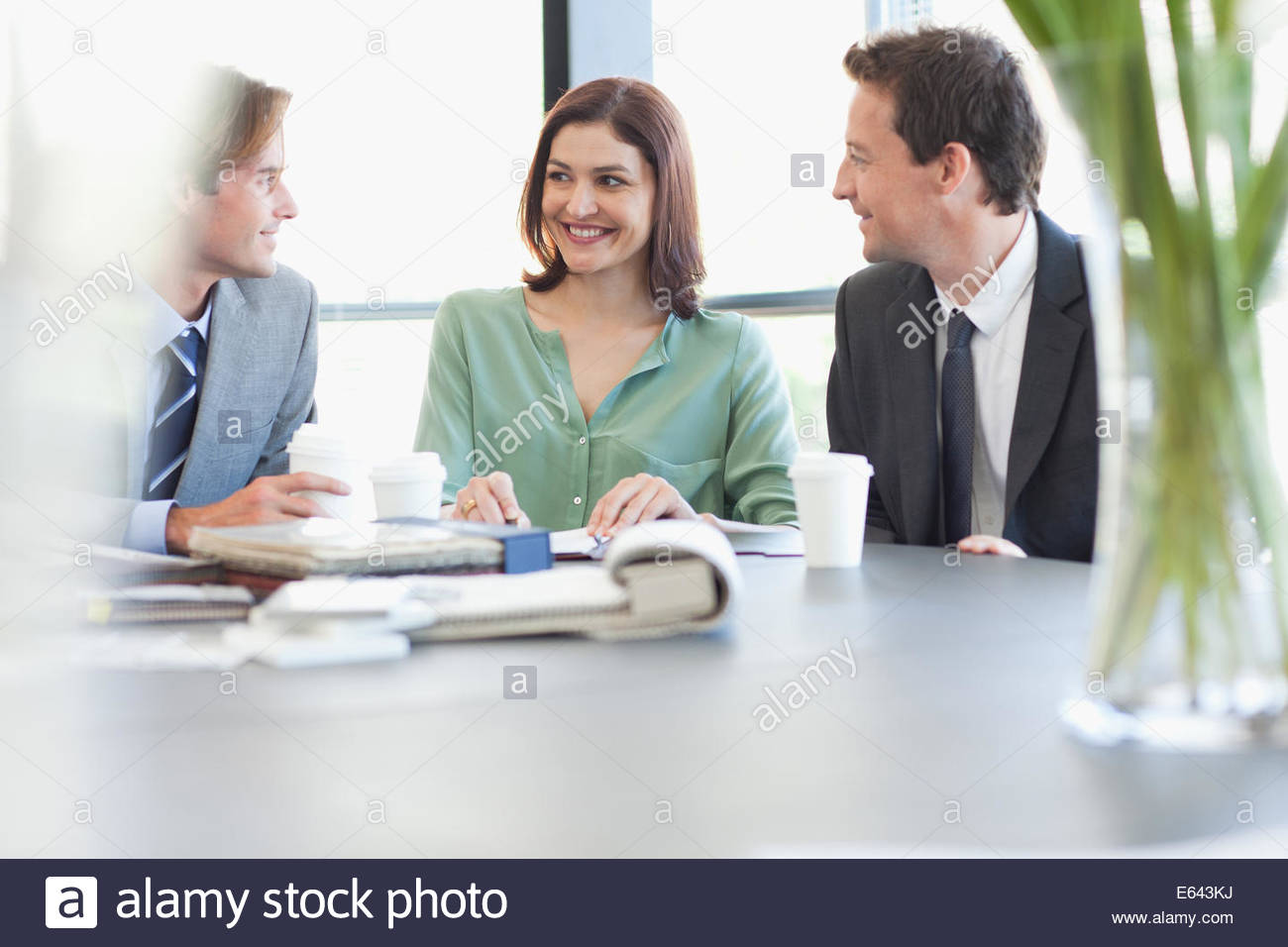 Portrait of smiling business people with coffee at table - Stock Image