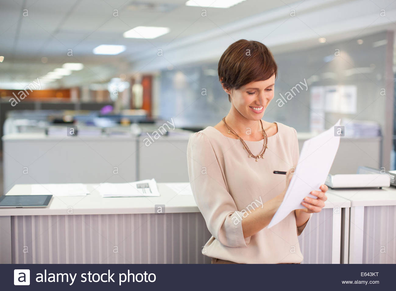 Businesswoman reviewing paperwork in office - Stock Image