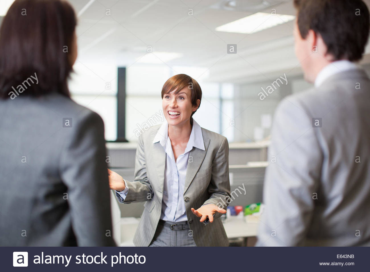 Businesswoman gesturing and talking to co-workers - Stock Image