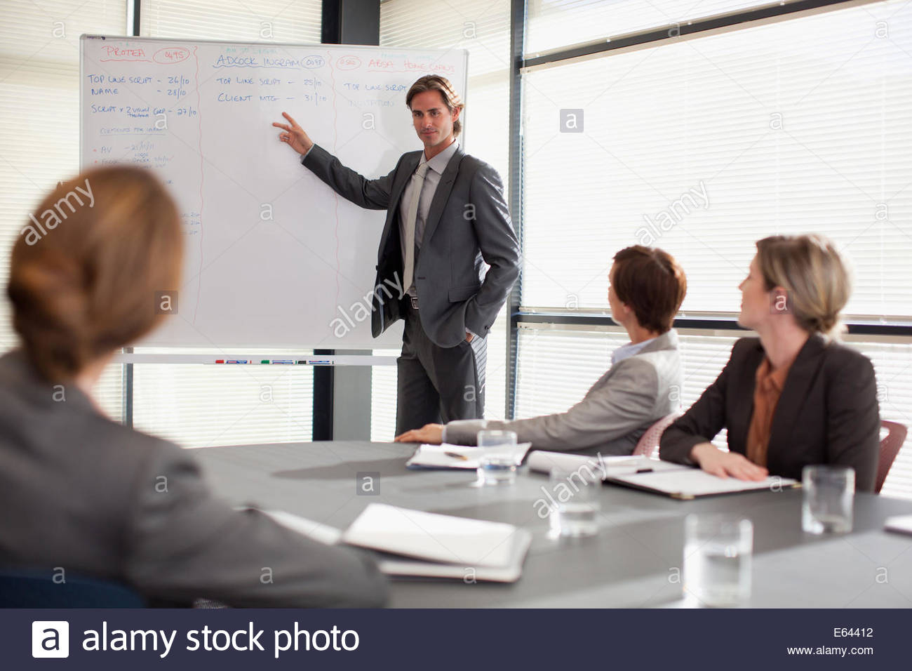Businessman at whiteboard presenting to co-workers - Stock Image