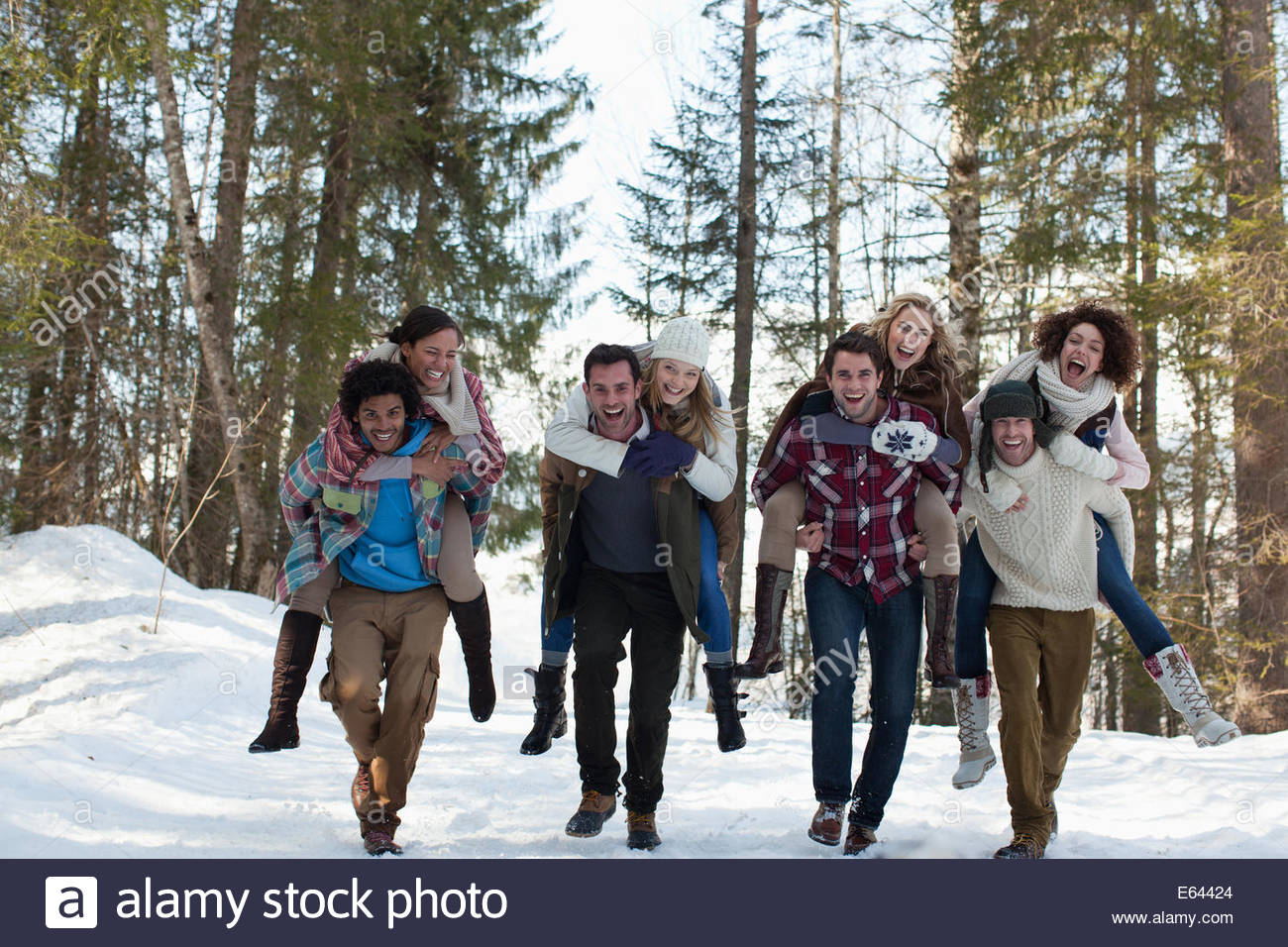 Enthusiastic couples piggybacking in snowy woods - Stock Image