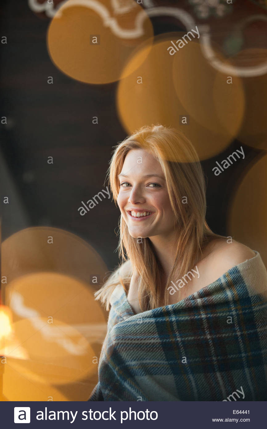 Portrait of smiling woman wrapped in a blanket - Stock Image