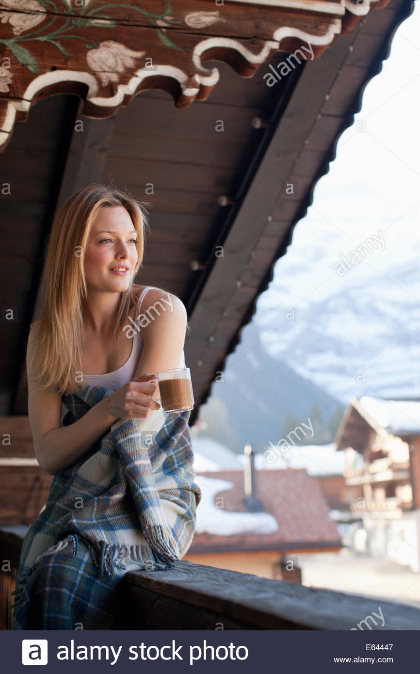 Smiling woman wrapped in a blanket and looking at view on cabin porch - Stock Image