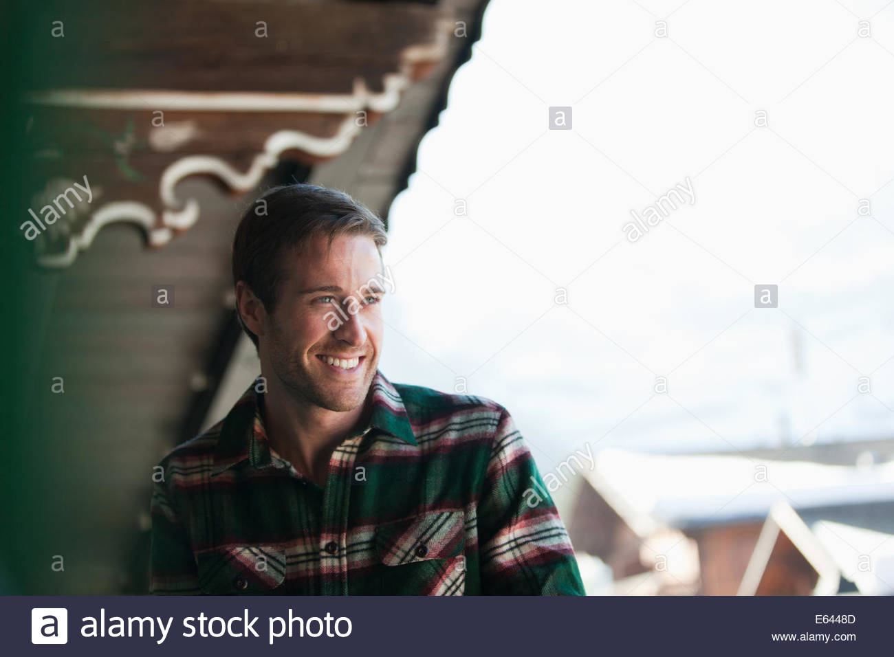 Man laughing on cabin porch - Stock Image