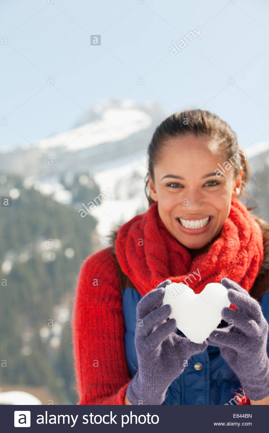 Portrait of smiling woman holding heart-shape snowball - Stock Image