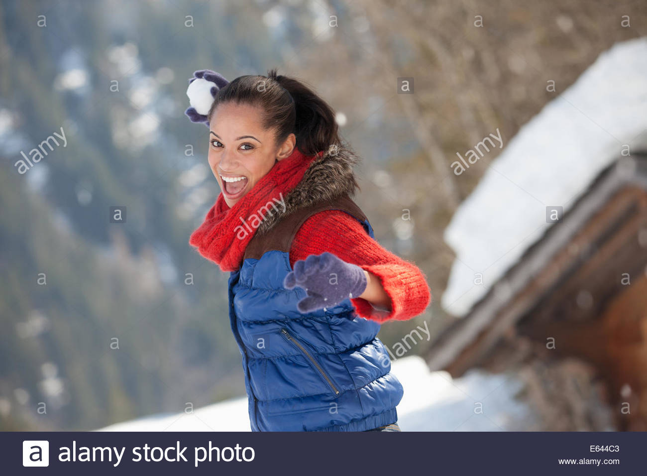 Portrait of smiling woman throwing snowball - Stock Image