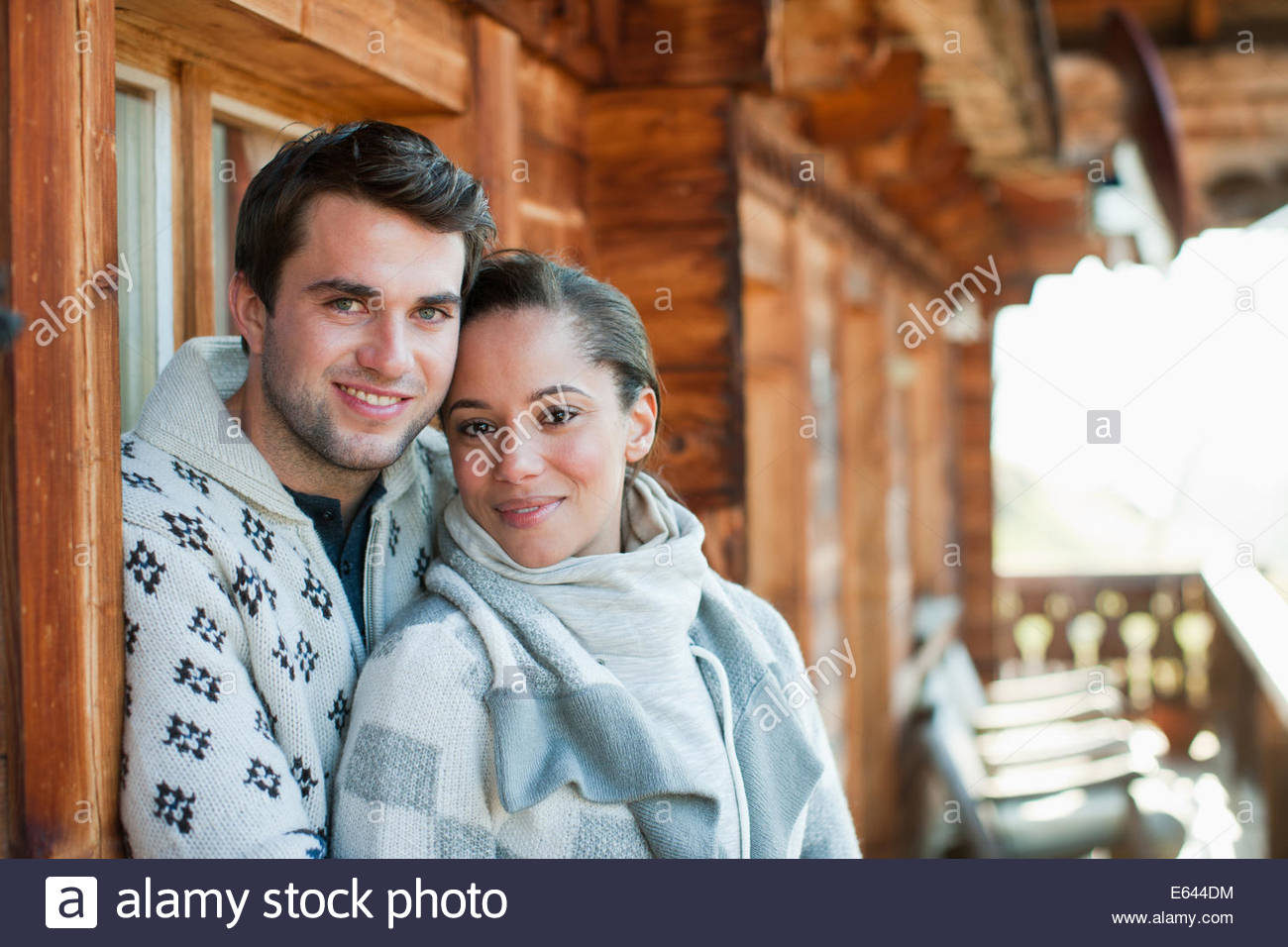 Portrait of smiling couple hugging on cabin porch - Stock Image