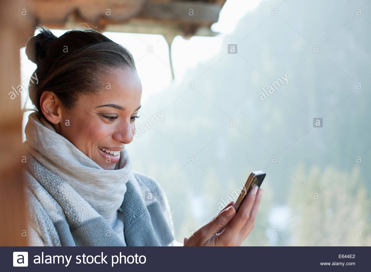 Smiling woman checking cell phone on cabin porch - Stock Image