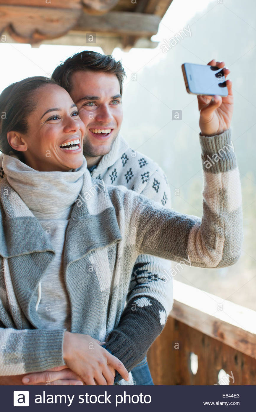 Smiling couple taking self-portrait with camera phone on cabin porch - Stock Image