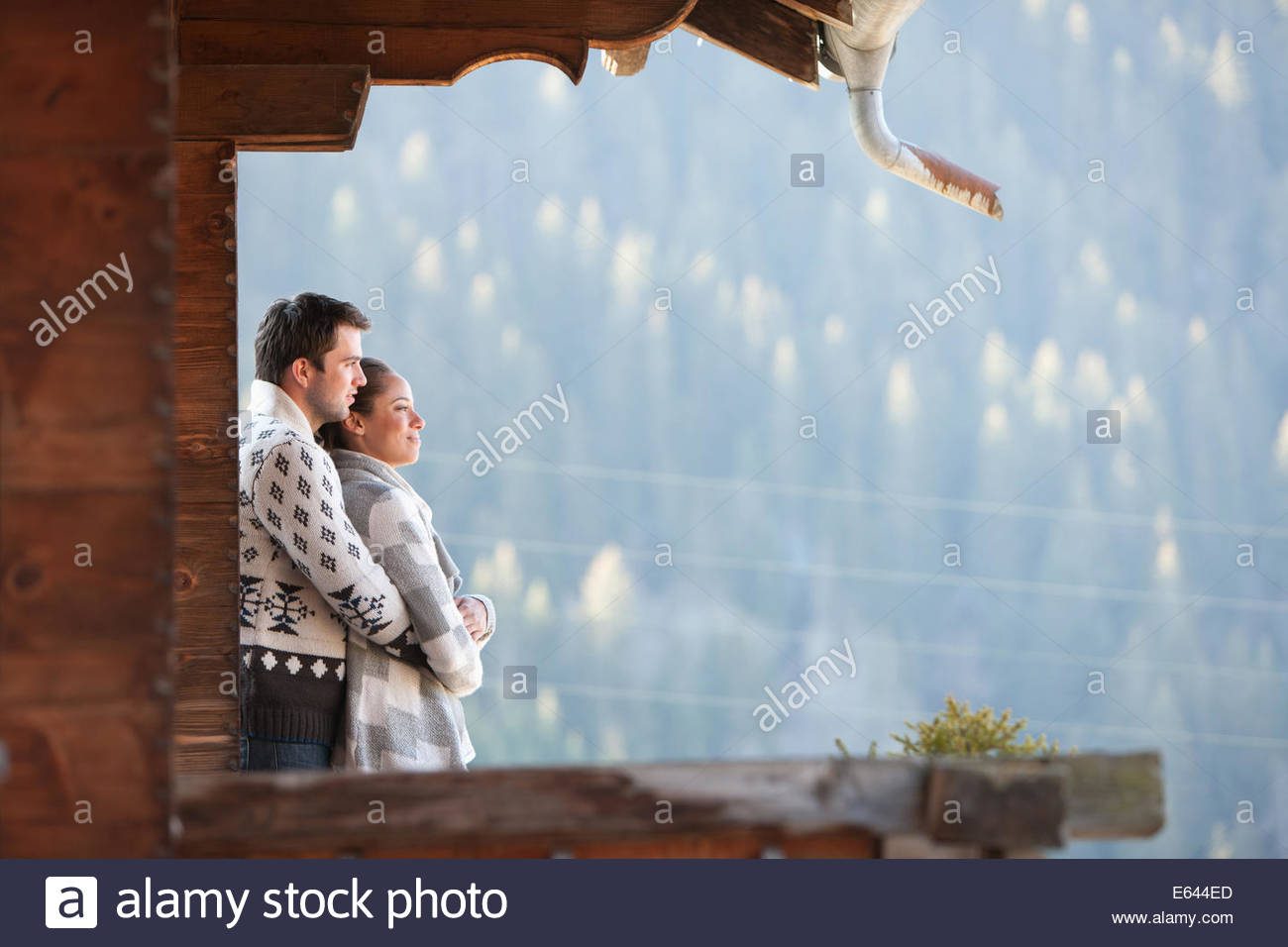 Couple hugging and looking at view from cabin porch - Stock Image