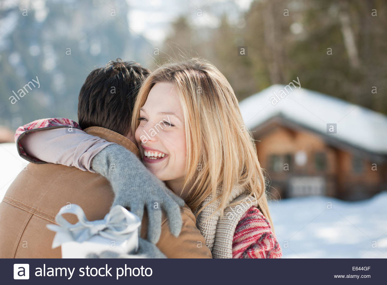 Smiling woman holding Christmas gift and hugging man in snowy field - Stock Image