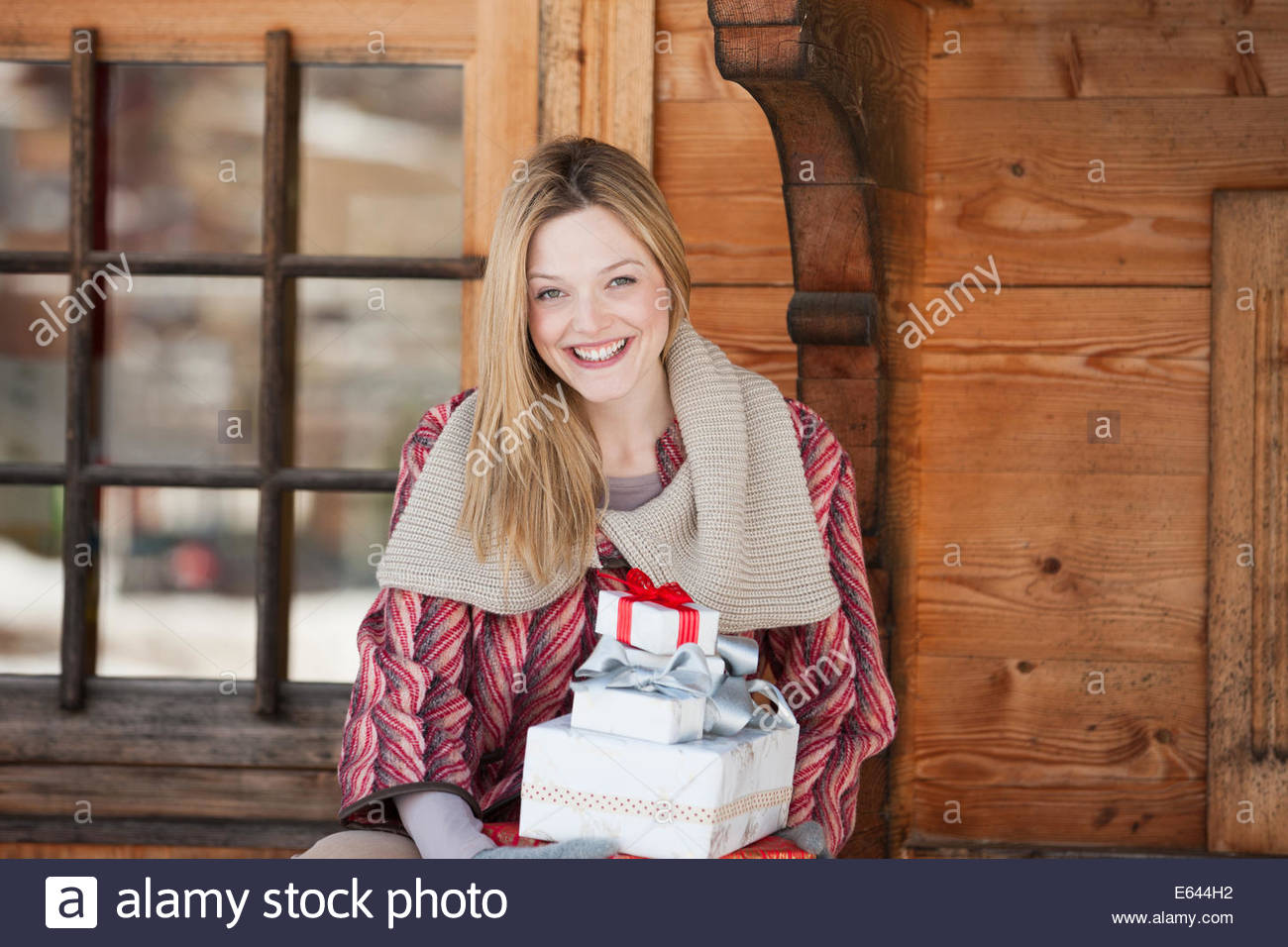 Portrait of smiling woman holding Christmas gifts on cabin porch - Stock Image